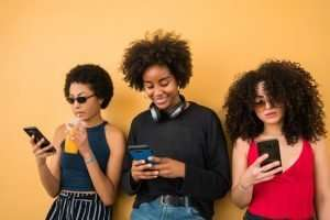 Three Afro friends using their mobile phone.
